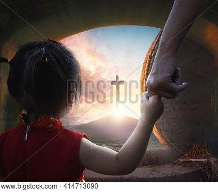 Easter Concept: Child's Hand Holding Mother's Finger On Blurred The Cross Of Jesus Christ Background