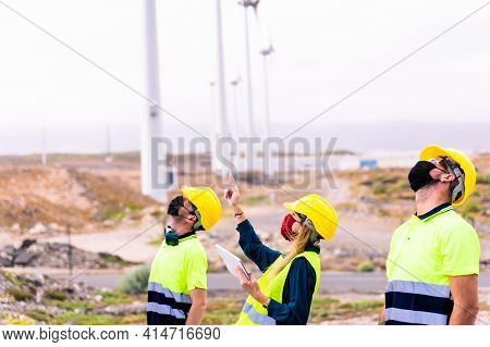 Woman Engineer And Skilled Workers Holding Yellow Safety Helmet With Standing And Checking Wind Turb