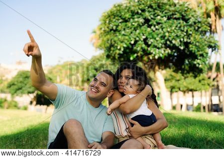 Family Laughing During Picnic In The Park. Young Cheerful Family Sitting On Grass Enjoying And Playi