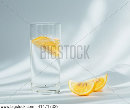 Glass Of Clean Mineral Sparkling Water With Ice And Lemon On A White Background With Sunshine. Light