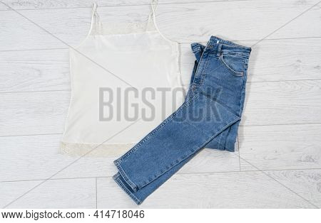 Blue Jeans Folded On White Wooden Background, Denim Folded On Light Wooden Background - Top View