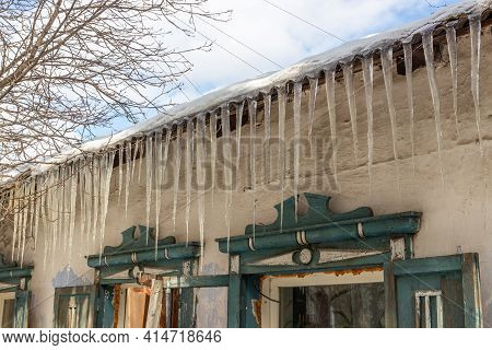 A Row Of Icicles Hangs From The Eaves Of The Roof Of A Village House