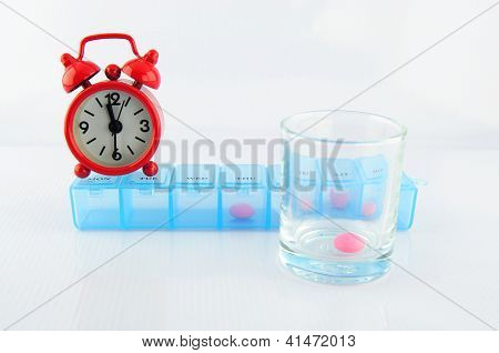 Pill Box And Pink Tablet In Glass At Medicine Time