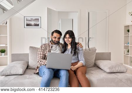 Happy Indian Family Couple Using Laptop Looking At Computer Sitting On Sofa Together Relaxing At Hom