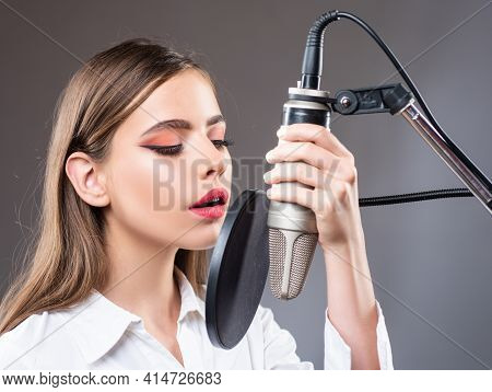 Young Woman With Microphone Singing Song. Musician In Music Hall. Funny Teen Singing In Karaoke