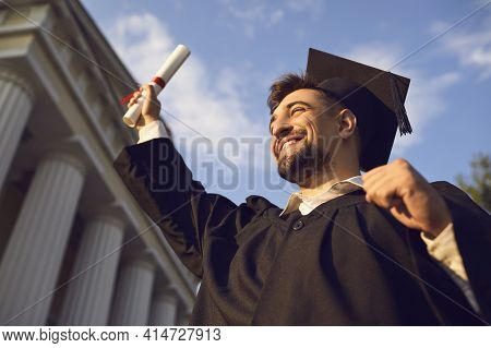 Portrait Of Overjoyed Young Graduate Holding Up His Diploma Celebrating College Graduation