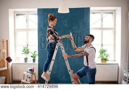 Mid Adults Couple Changing Light Bulb Indoors At Home, Relocation And Diy Concept.