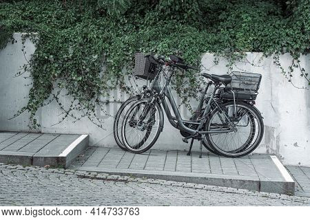 Two Bicycles Parked On The Sidewalk Near A Concrete Wall And Green Vegetation. Bicycles On The Sidew