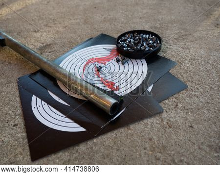 A Target For Shooting And The Barrel Of An Air Rifle. Shooting Target With Bullets And Rifle Barrel