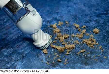 The White Mini Portable Vacuum Cleaner Removes Dirt. Bread Crumbs. On A Blue Background