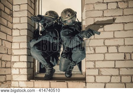 Group Of Special Forces Fighters Storm The Building Through The Window. Training Sessions Of The Swa