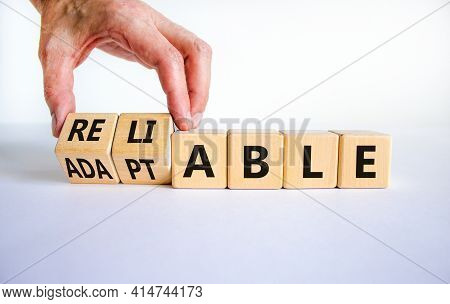 Adaptable Or Reliable Symbol. Businessman Turns Wooden Cubes And Changes The Word Adaptable To Relia