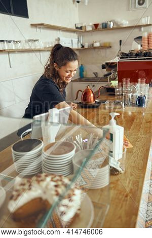 Young Woman Barista With Standing And Cleaning The Bar Counter In A Coffee Shop, Disinfecting Counte