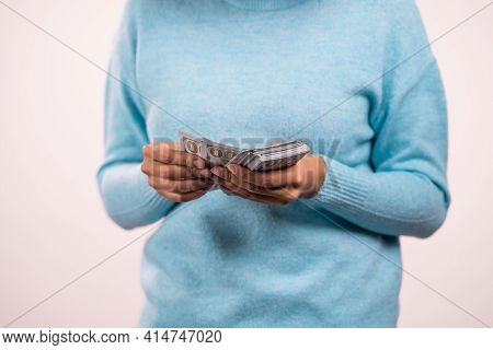 Hands Of Woman Counting Usd Currency. Lady Counts Money - Dollars Banknotes On White Wall. Symbol Of