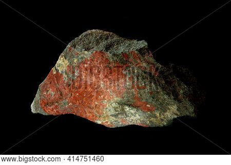 Red Rhodonite Mineral Blotch In Rock Isolated On Black Background. Found In Crimea. For Geology Or M