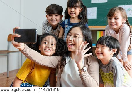 Asian Teachers Use Smartphones To Take Selfies With A Group Of Deversity Elementary School Students