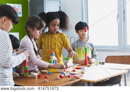 Group Of Diversity Of School Students Playing Wooden Blocks In Classroom. Elementary School Children