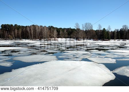 Natural Landscape With Ice Drift On The Spring River And Forest Trees On Opposite Bank Under Cloudle