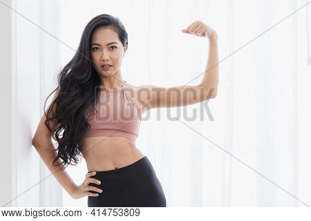 A Beautiful Asian Women's Fitness At Home Instead Of Going To The Fitness Gym.her Showing Muscles Of
