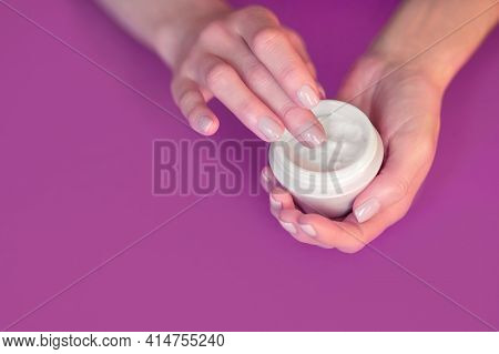 Female Hands Hold A Container With Hand Or Face Cream. Using A Moisturizer In Daily Life To Nourish