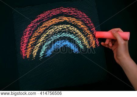 The Child Draws A Rainbow On A Rough Black Board. Self-development And Drawing Training. Hand Draws