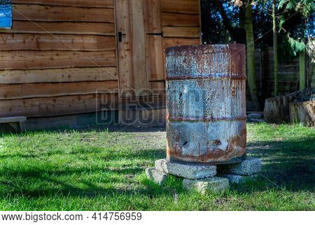 Rusty Old Charred Fire Steel Drum Sitting On Concrete Blocks On A Garden Lawn. Waney Edge Wooden Gar