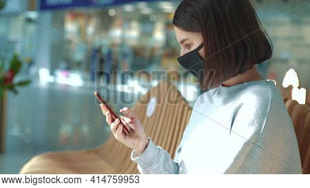 Girl In Mask Smartphone Shopping. A Girl In Black Protective Mask Shop In Purchases On Smartphone. O