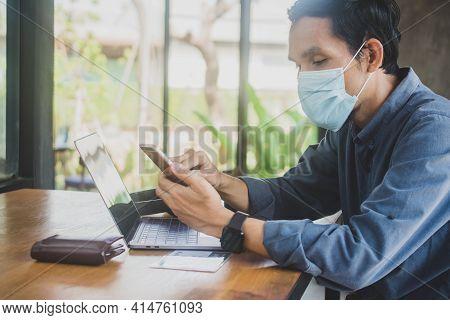 Man Wear Facemask Working Laptop  In Cafe , People Using Phone