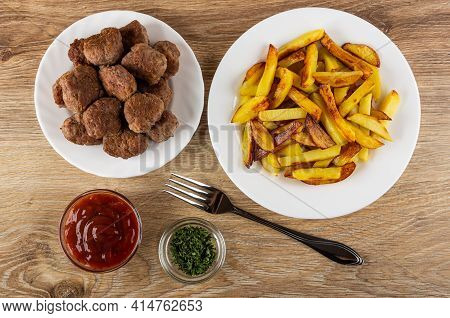 Plate With Fried Meatballs, Pieces Of Fried Potato In White Glass Plate, Transparent Bowls With Drie