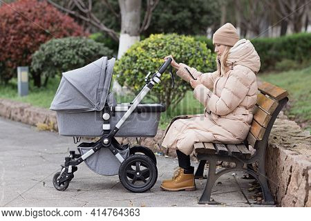 Happy Mother Walking With Stroller In Park And Using Mobile Phone. Joy Of Motherhood. Stylish Young