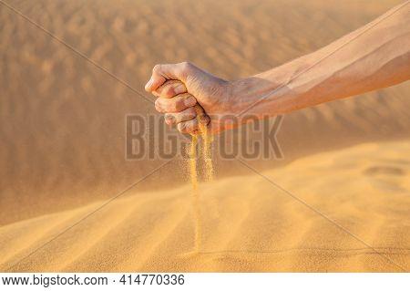 Desert, Sand Puffs Through The Fingers Of A Mans Hand