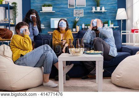 Multiethnic Friends Socialising Looking At Terrifying Movie On Tv