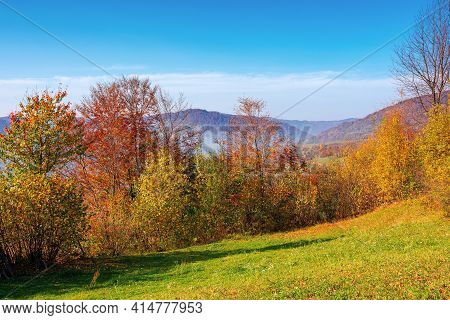 Mountainous Rural Scenery In Fall Season. Trees The Hill In Colorful Foliage. Village In The Distant