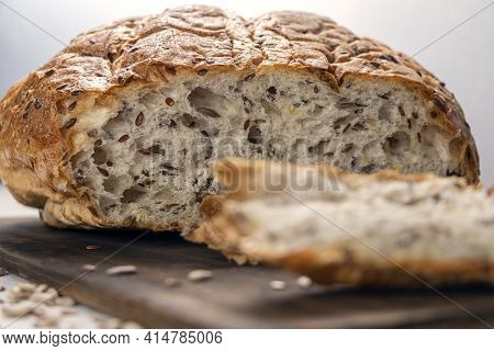 Close Up Sliced Bread On Serving Board With Flax And Sunflower Seeds. Fresh, Tasty, Round Wheat Brea
