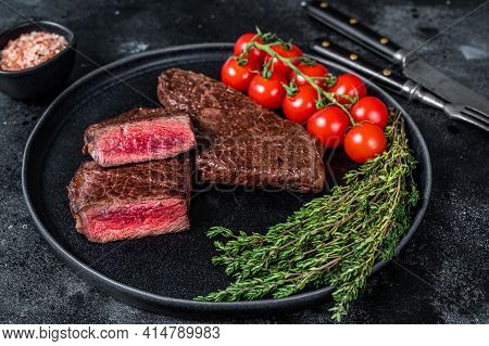 Roasted Cut Denver Beef Meat Steak On A Plate With Thyme. Black Background. Top View