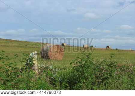 A Kansas Country Landscape With A Limestone Fence, Blue Sky , Clouds, And A  Pasture With Alfalfa Ba