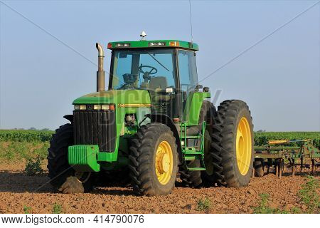 A John Deere Tractor In A Farm Field With An Implement On The Back With A Crop Growing In The Field