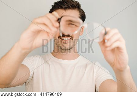 Man Holding Glasses For Vision And Looking Through Them To The Camera, Indoors. Young Man Squints, P