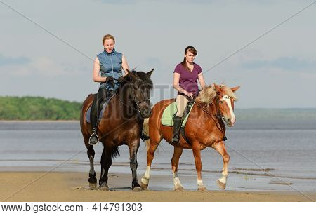 Two Caucasian Women Are Riding On Horseback On Beach Near A Water.