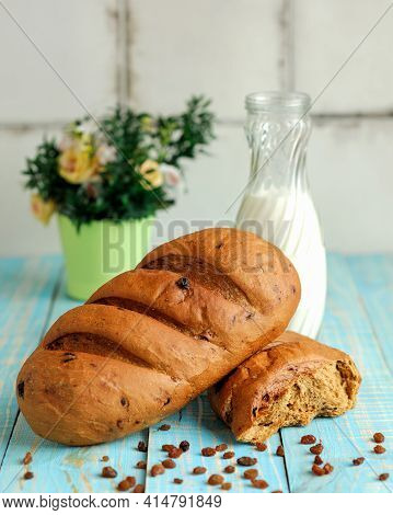 Loaf Of Wheat Bread With Raisins And Milk Bottle On Kitchen Table. Light Breakfast And Flower Pot On