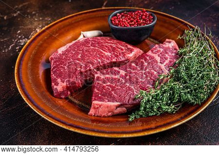 Fresh Raw Denver Or Top Blade Meat Steak On A Rustic Plate With Thyme. Dark Background. Top View