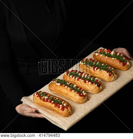 Woman In Black Holds Snack. Homemade Vegan Sandwiches With Ketchup And Mayonnaise On Parchment Paper