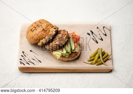Tasty Grilled Double Meat Burger With Cucumbers, Tomatoes And Green Peppers On Paper. Set Of Ingredi