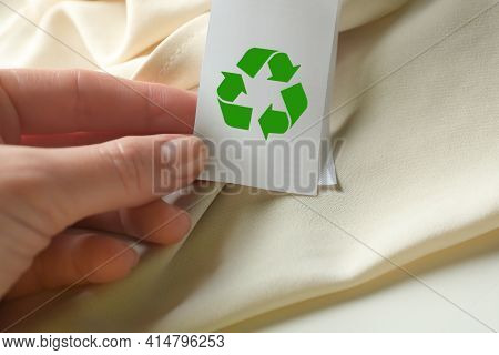 Woman Showing Clothing Label With Recycling Symbol On Beige Garment, Closeup