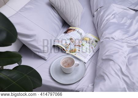 Cup Of Coffee And Magazine On Bed With Soft Silky Bedclothes