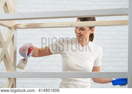 Close Up Of Young Brunette Smiling And Painting In White Color Rack At Home. Concept Of Process Impr