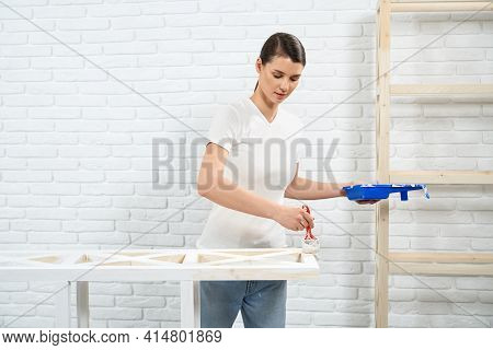 Young Brunette Woman Painting Wooden Rack In White Color At Home. Concept Of Improvement Wooden Rack