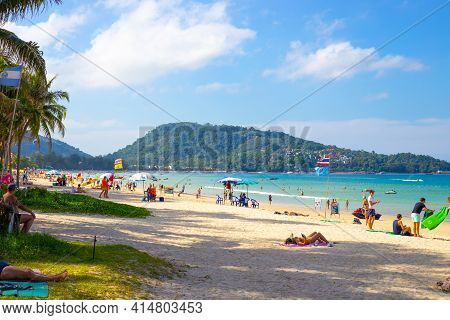 Phuket, Thailand-29.12.2018: Coast Of Patong Beach On A Sunny Day With Tourists Resting. Leisure And