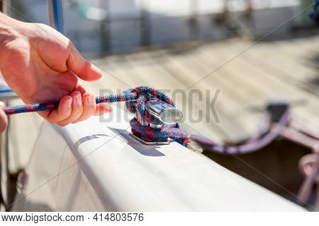 Man Hand With Boat Rope, Yachtsman Tying Sea Knot. Human Hand On Sailing Boat Or Yacht Tying A Knot,