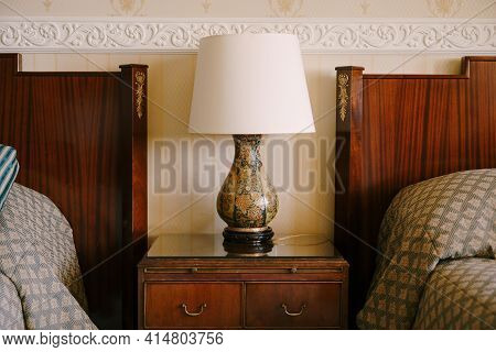 Bedside Lamp On The Nightstand. Refined And Rich Interior. Wooden Bedside Table Next To Two Beds.